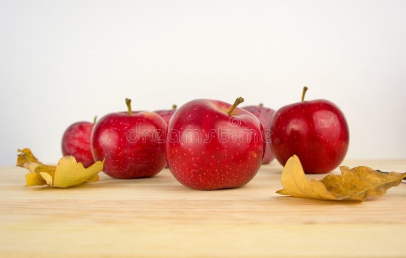Confine d'annata di autunno dalle mele e dalle foglie cadute su vecchio woode immagini stock