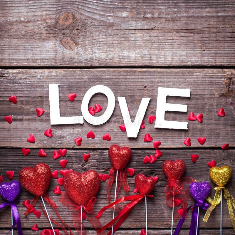 Confine dai cuori rossi, della viola e dell'oro e dall'amore decorativi di parola su fondo di legno d'annata fotografie stock libere da diritti