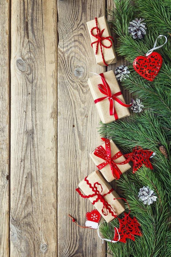 Confine dai rami del pino, dalle decorazioni di Natale e dai contenitori di regalo su una vecchia tavola di legno Fondo di Natale fotografia stock libera da diritti