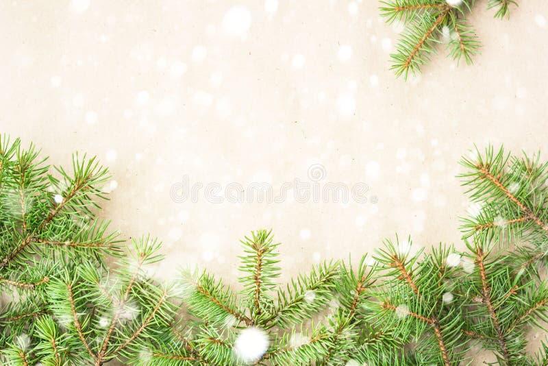 confine dei rami dell'abete con neve su fondo rustico leggero, buon per il contesto di natale immagini stock