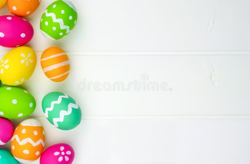 Confine del lato dell'uovo di Pasqua contro legno bianco fotografia stock