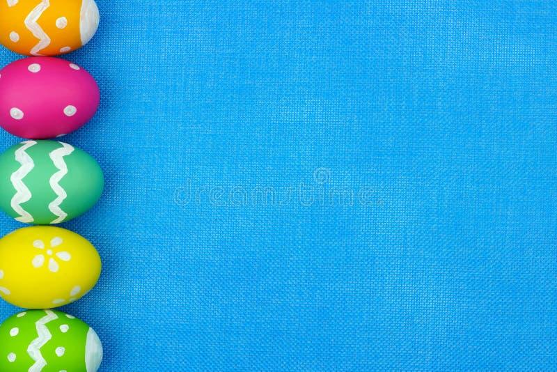 Confine del lato dell'uovo di Pasqua sopra il fondo blu della tela da imballaggio fotografia stock libera da diritti