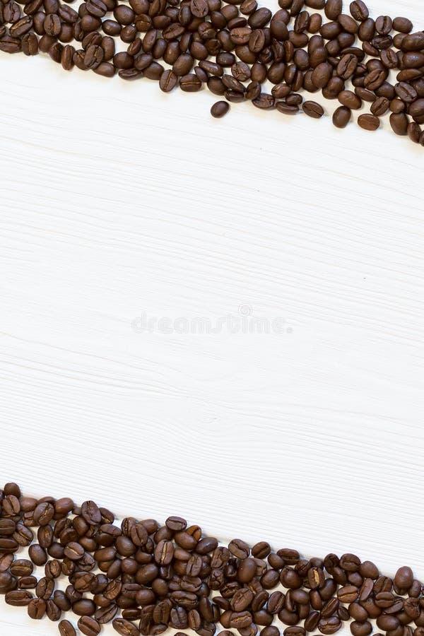 Confine della struttura dei chicchi di caffè nero, grani di diagonale su fondo di legno bianco strutturale immagine stock
