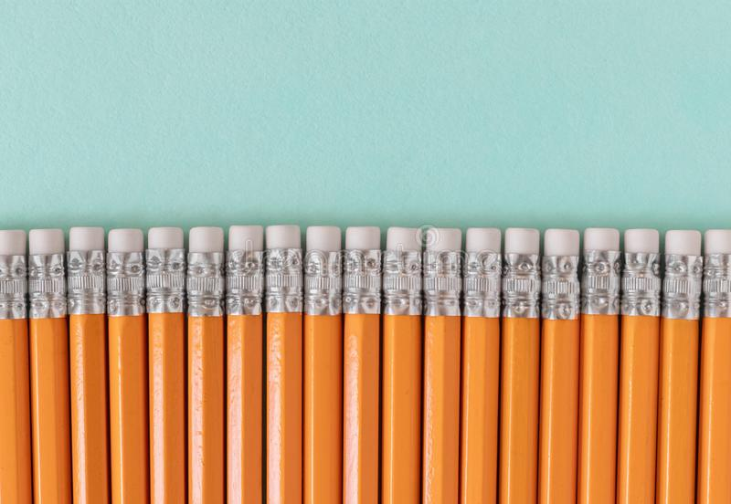 Confine delle matite arancio con le gomme, su un fondo verde blu con lo spazio della copia fotografie stock libere da diritti
