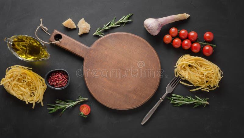 Confine delle tagliatelle crude asciutte della pasta, pomodori, basilico, parmigiano per la cottura dei piatti Mediterranei Spazi fotografie stock libere da diritti