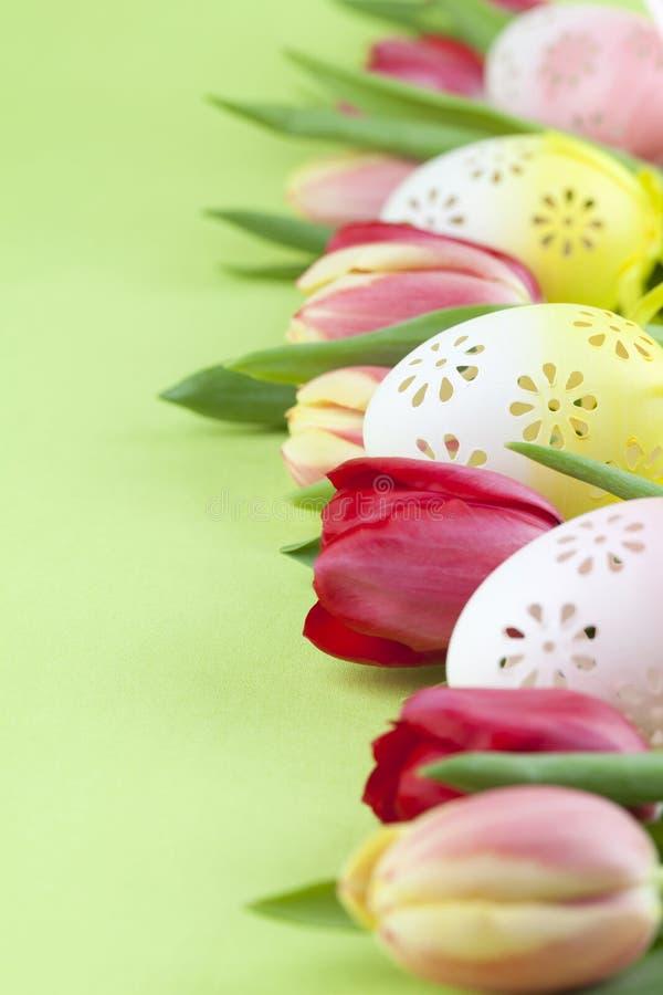 Confine fiorito delle uova di Pasqua e dei tulipani immagini stock libere da diritti