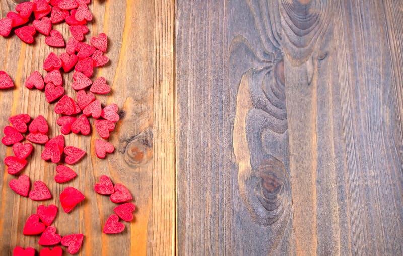Confine fatto di pochi cuori rossi della caramella sui precedenti di legno immagine stock