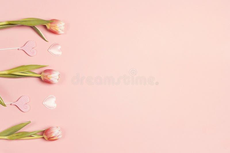 Confine floreale con i fiori ed i cuori dei tulipani su fondo pastello rosa fotografia stock libera da diritti