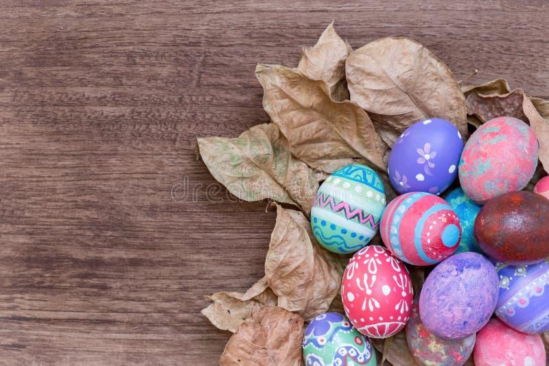 Confine variopinto del lato dell'uovo di Pasqua contro un PA del legno rustico dell'annata fotografia stock libera da diritti