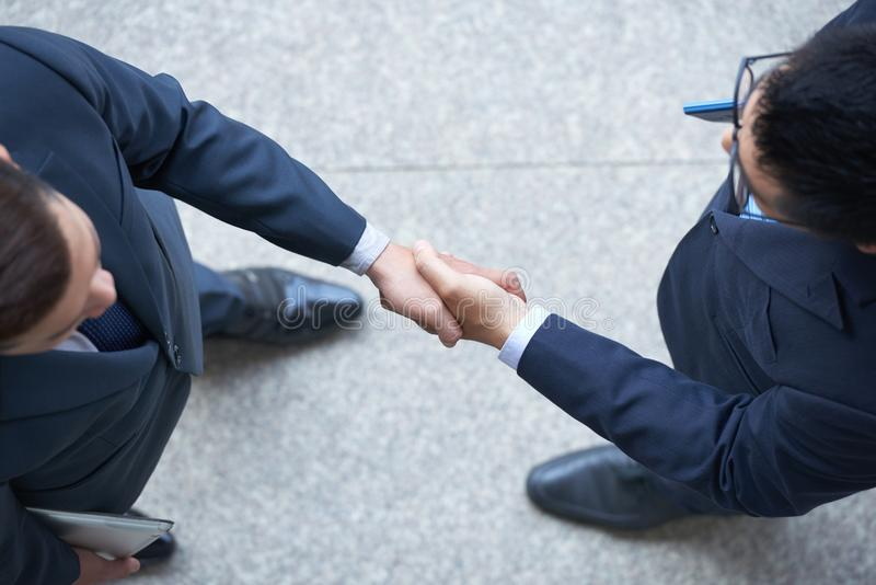 Confirming deal. Business partners shaking hands to confirm the deal royalty free stock images