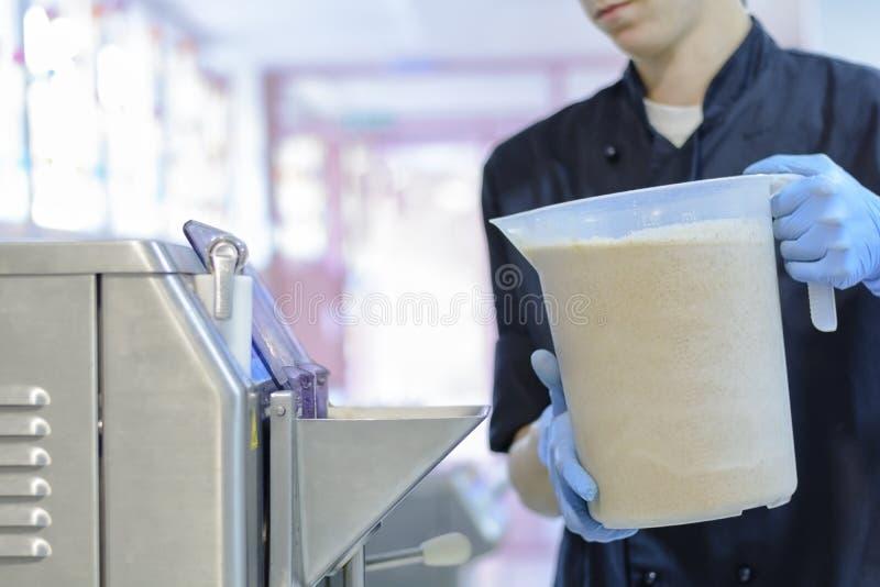 Confiseur de chef dans l'uniforme produisant la crème glacée avec la machine de crème glacée  photographie stock