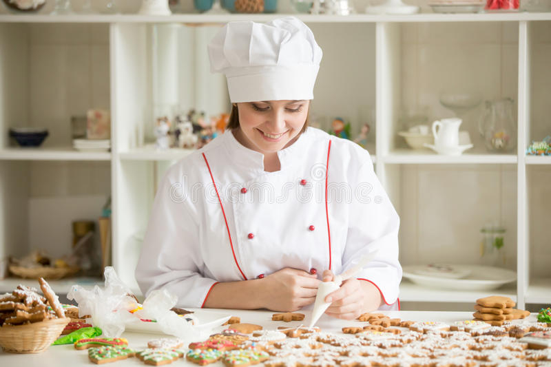 Confiseur de sourire professionnel décorant des étoiles de pain d'épice image stock