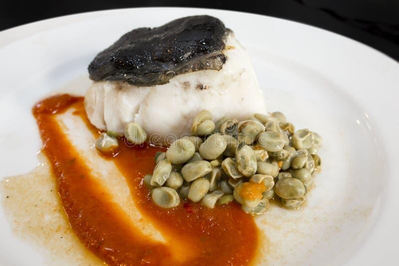 Confit av torskfilén, över tomatdriftstopp och Ali Oli av svart vitlök arkivfoto