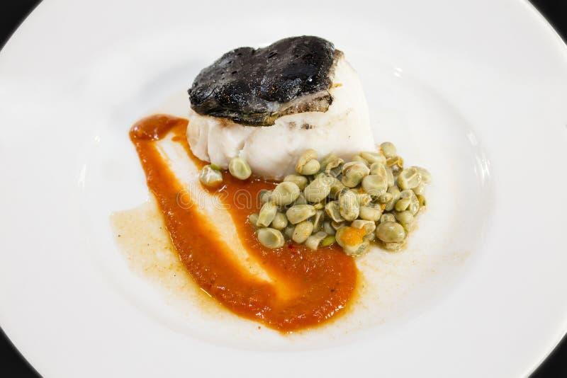 Confit av torskfilén, över tomatdriftstopp och Ali Oli av svart vitlök royaltyfri fotografi