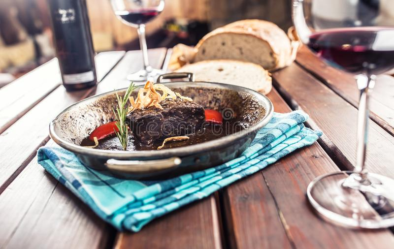 Confit beef steak with sauce fried onion bread red wine and deco. Ration in pub or restaurant royalty free stock image