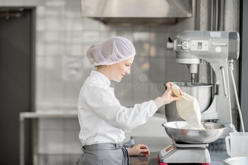 Confitero de la mujer que trabaja en la fabricación de la panadería imagen de archivo