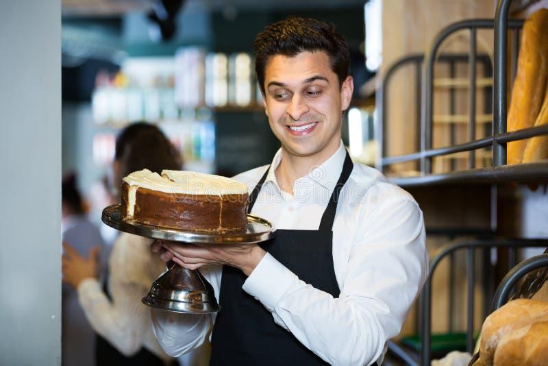 Confitero del hombre que sostiene la torta deliciosa fotografía de archivo