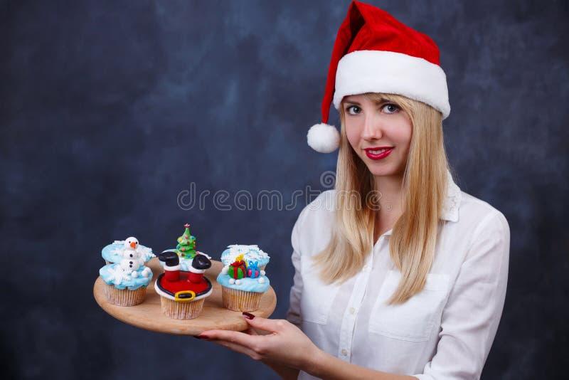 Confitero hermoso joven de la mujer en el casquillo de Papá Noel con C adornada fotografía de archivo