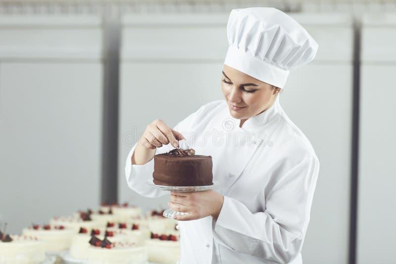 Confitero que adorna la torta de chocolate en tienda de pasteles imagen de archivo libre de regalías