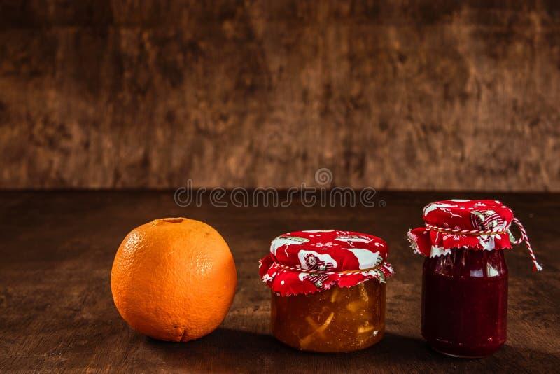 Confiture avec le fruit sur un fond rustique photo stock