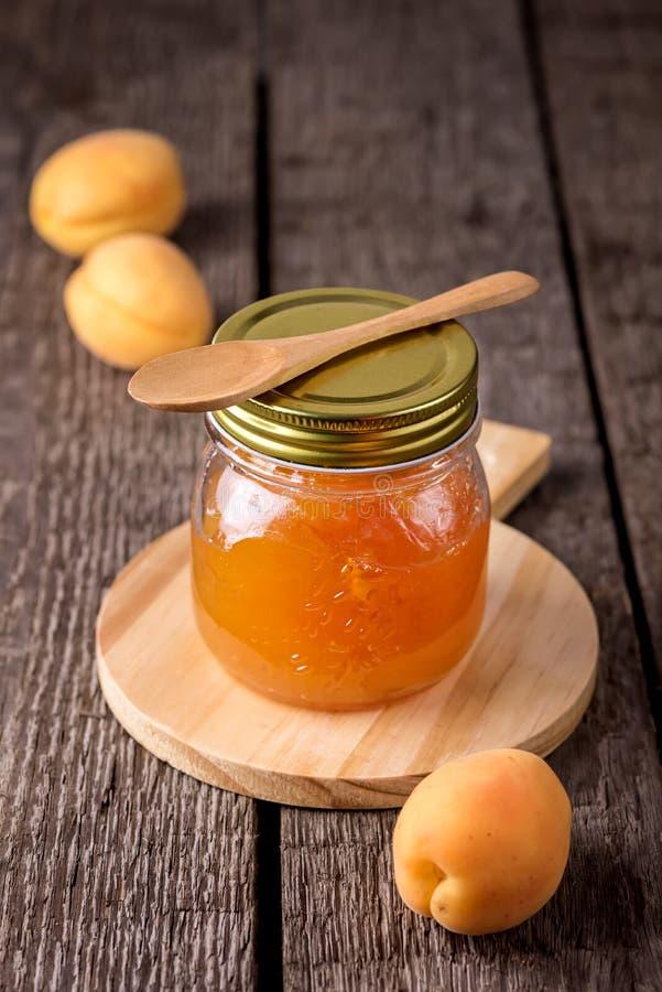 Confiture d'abricot dans un pot en verre et des abricots frais sur le conseil fait maison savoureux d'Autumn Harvesting Vertical  photographie stock libre de droits
