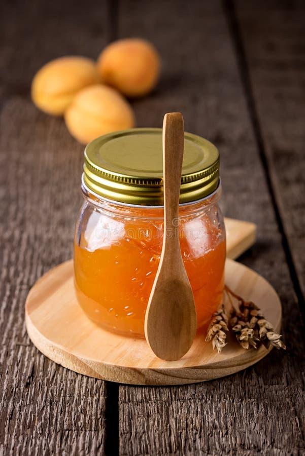 Confiture d'abricot dans un pot en verre et des abricots frais sur le conseil fait maison savoureux d'Autumn Harvesting Vertical  image stock