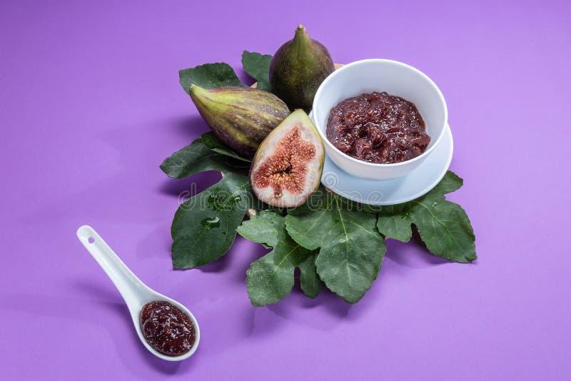 Confiture de figue avec des figues, des feuilles de figue et la cuillère blanche avec la confiture sur le fond pourpre photographie stock libre de droits