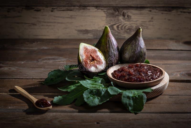 Confiture de figue avec des figues, des feuilles de figue et la cuillère en bois avec la confiture sur le fond en bois photo stock