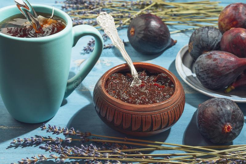 Confiture de figue dans un bol, des figues fraîches, et une tasse de thé sur un fond en bois Concept savoureux sain de petit déje image stock