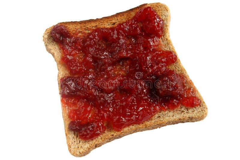 Confiture de fraise répandue sur le pain grillé. image stock