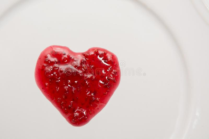 Confiture de framboises sous forme de coeur d'isolement sur le blanc images stock