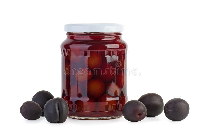 Confiture en verre avec prunes conservées et baies à proximité photo stock
