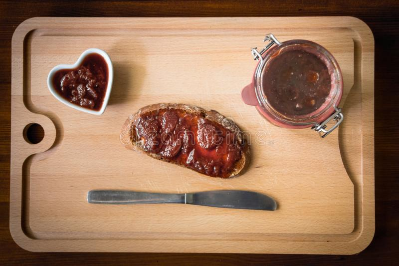 Confiture faite maison avec du pain et un couteau photo stock