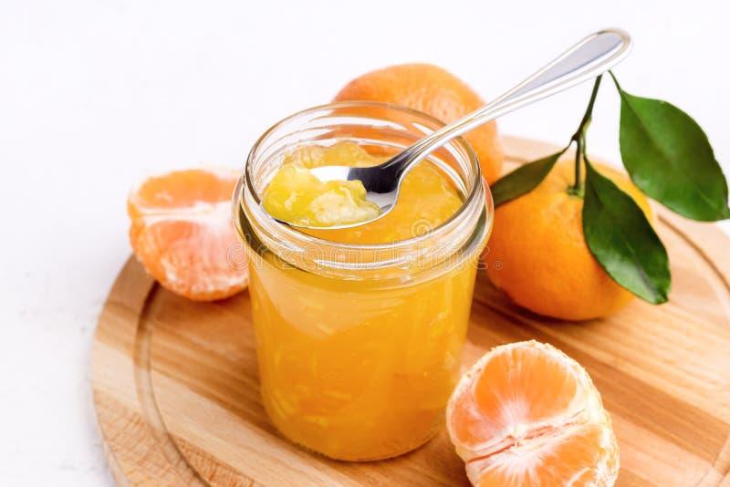 Confiture savoureuse de mandarine d'agrume à un arrière-plan blanc de pot en verre ci-dessus photo libre de droits