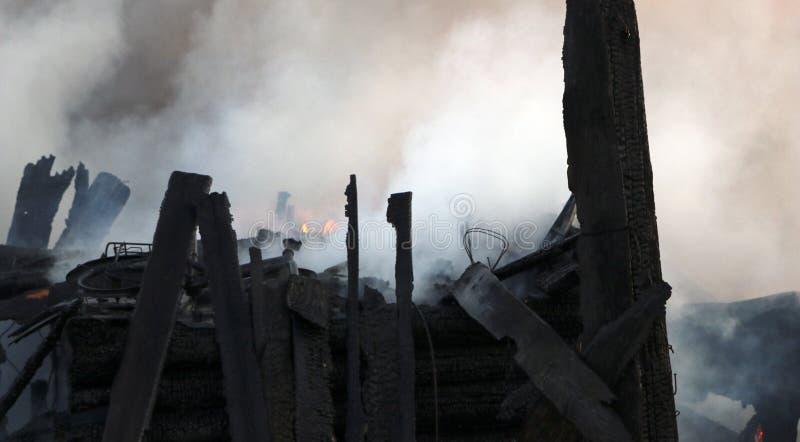conflagration ruínas e sobras de uma casa de madeira queimada Lenha carbonizada queimada no fumo grosso fotografia de stock
