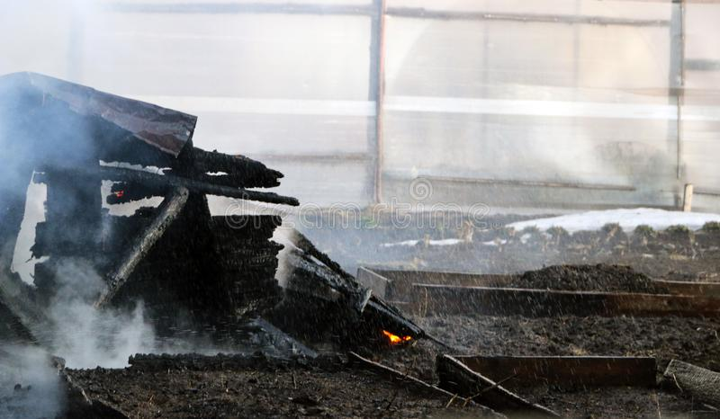 conflagration ruínas e sobras de uma casa de madeira queimada Lenha carbonizada queimada no fumo grosso foto de stock royalty free
