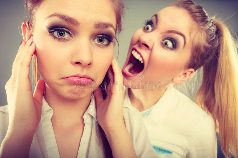 Fury girl screaming at her friend, female closing his ears. Conflict, bad relationships, friendship difficulties. Two young women having argument. Angry fury stock images