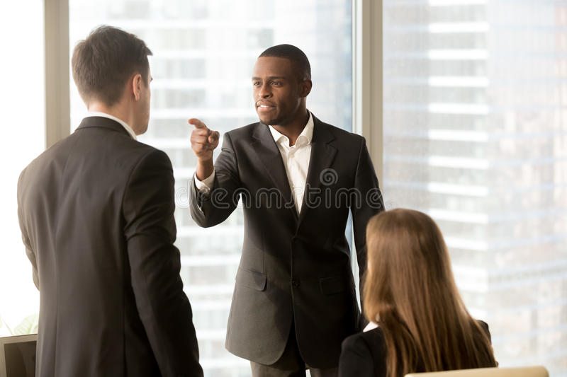 Conflict between male black and white office workers at workplac. Angry african-american businessman threatens colleague, conflict between male workers at stock photography