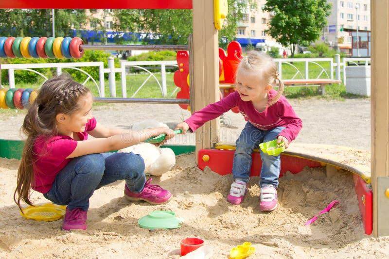 Conflict op de speelplaats Twee jonge geitjes die over een stuk speelgoed schop in de zandbak vechten royalty-vrije stock afbeeldingen