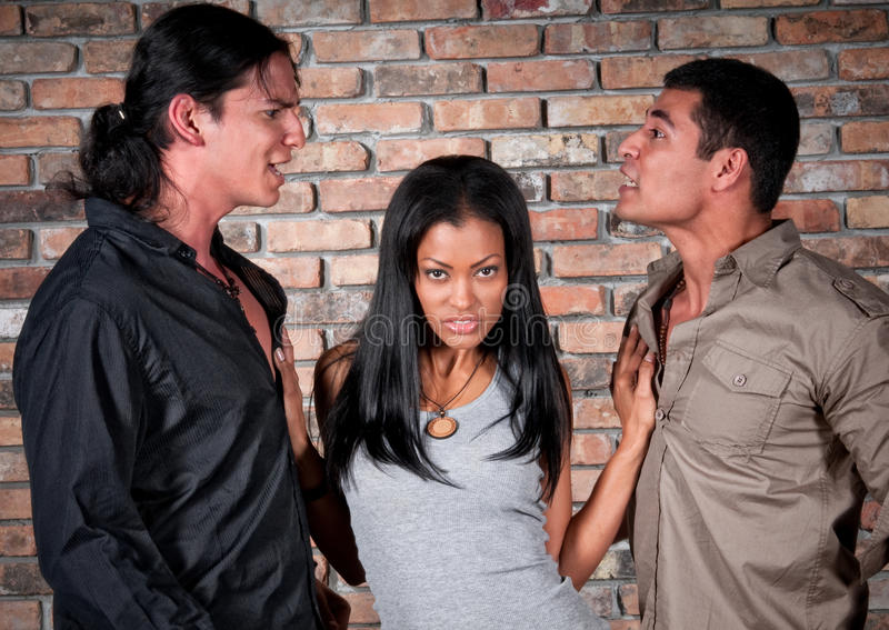 Conflict over girl. 2 handsome guys arguing over a very sensual latin girl royalty free stock photos