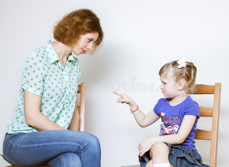 Conflict tussen jonge moeder en haar weinig dochter stock foto