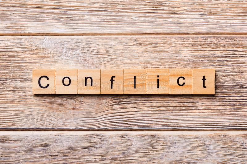 CONFLICT word written on wood block. CONFLICT text on wooden table for your desing, concept.  stock photo