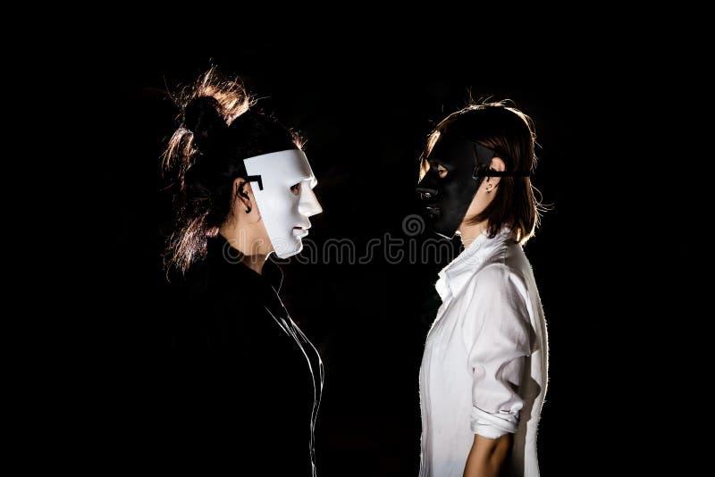 Conflictconfrontatie tussen mooie vrouw in zwart masker en stock fotografie