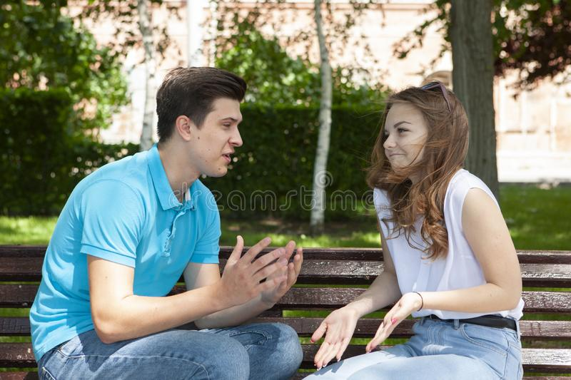 Conflicted couple not talking to each other seated on a wooden bench in park stock photography
