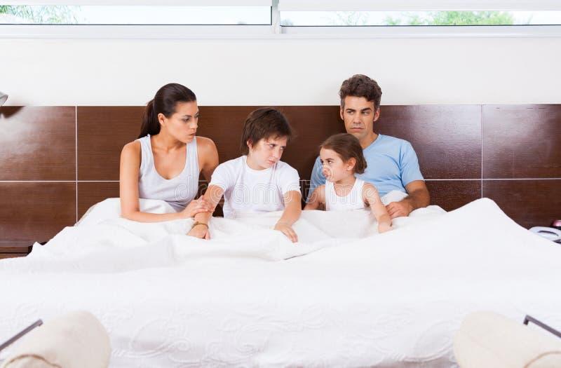 Conflictfamilie die in een bedcouple met kinderen liggen royalty-vrije stock fotografie