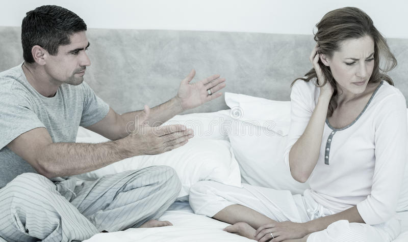 Conflicting couple in bed. Mid adult couple arguing in bedroom stock images