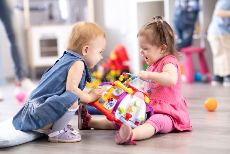 Conflicto en el patio Dos niños que luchan sobre un juguete en guardería foto de archivo