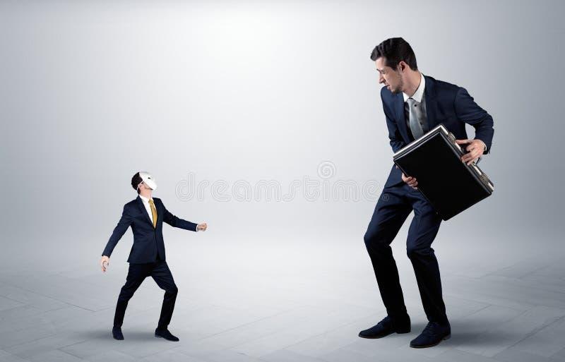 Conflicto entre el hombre de negocios pequeño y grande fotografía de archivo