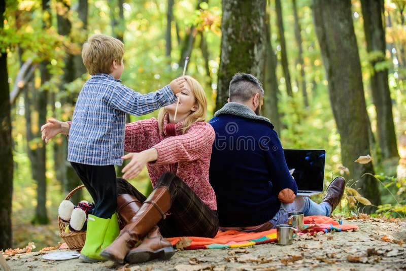 Conflicts of being dad. Family and career goals. Dad is always busy. Family day concept. Family with kid boy relaxing in. Forest. Mother and little play royalty free stock photography