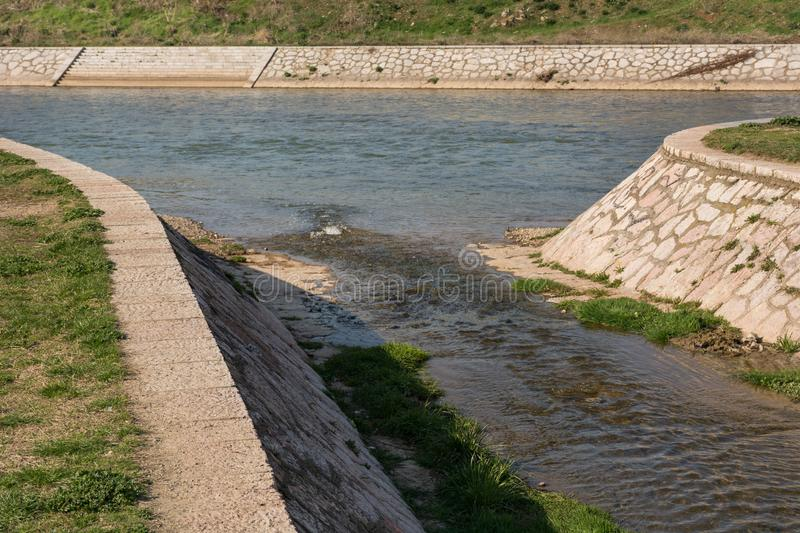 Confluence of the small to big river with rock quay on sunny spring day in city park royalty free stock images
